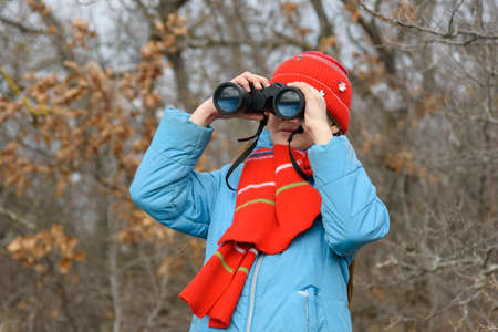 Girl enthusiastically looks through binoculars, front view, close-up