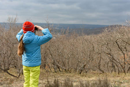 A girl in an autumn day looks through binoculars from the mountain, back view Standard-Bild
