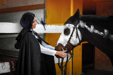 A beautiful girl in medieval style clothes looks at a horse painted with white paint with a painted skeleton Standard-Bild