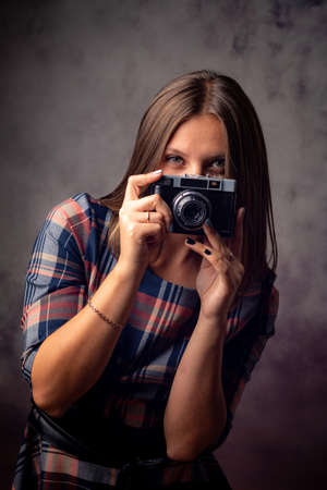 Girl photographer peeking out from behind the camera, half-length studio portrait on a gray background
