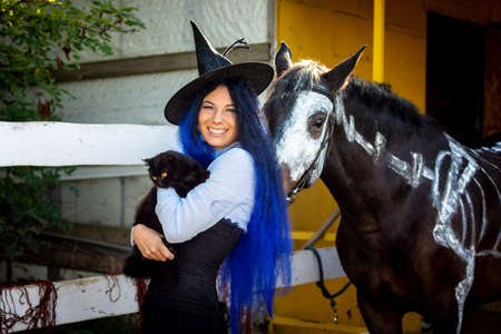A girl dressed as a witch holds a black cat in her arms and stands by a corral on a farm next to a horse
