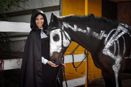 A beautiful girl in medieval style clothes looks happily into the frame and feeds a horse painted with white paint with a painted skeleton