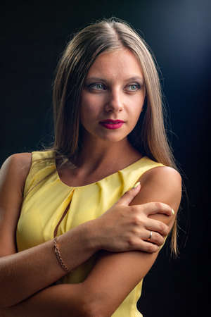 Portrait of a beautiful girl in a yellow dress on a black background
