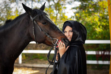A girl in a black cloak hugs the muzzle of a horse against the background of trees and a fence