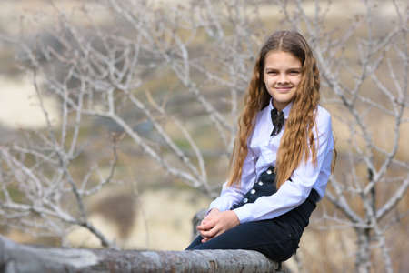 A girl sits on a wooden fence and looks happily into the frame Standard-Bild