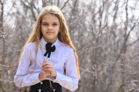 Portrait of a beautiful twelve-year-old girl with dried wildflowers in her hands on a forest background Standard-Bild