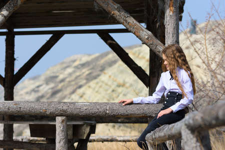 A girl sits on a wooden fence near an old gazebo made of wooden beams