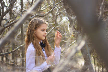 A girl stands with dried wildflowers, in the foreground and background blurred branches of bushes in the forest