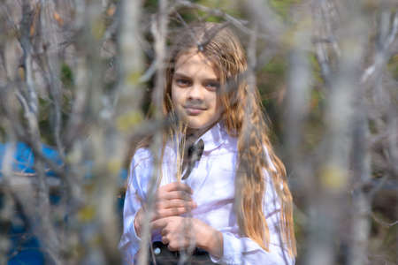 A girl stands with dried wildflowers, in the foreground blurred branches of bushes Standard-Bild