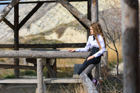 A girl sits on a wooden fence near an old gazebo made of wooden beams on a sunny warm day Standard-Bild