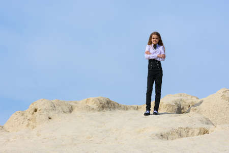 A girl in a white shirt with a bow tie stands on a mountain against the background of the sky