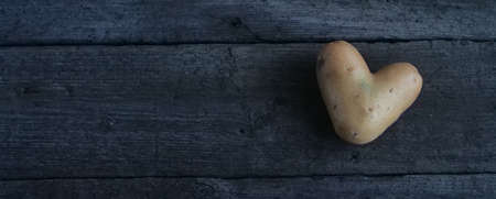 Heart shaped potato on a wooden table