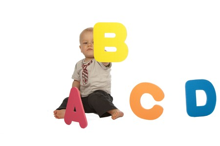 Little Baby Boy Sitting in Front of Colourful Letters