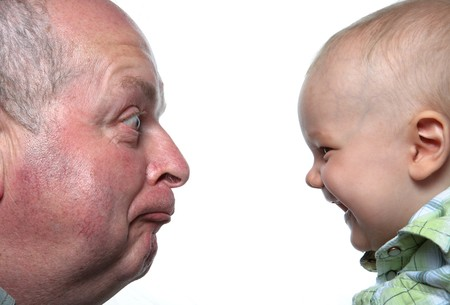 sons and grandsons: Little Baby Boy Laughing At Aged Man In His Face Stock Photo