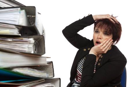 Gestresst Arbeitnehmer an Ihrem Schreibtisch mit Dateien auf White Isolated Background