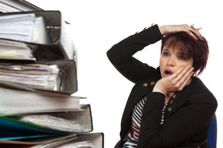 Stressed Out Worker At Her Desk With Files On White Isolated Background Stock Photo