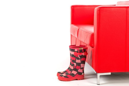 Pair of Stylish Wellingtons in front of a Red Couch on a White Isolated Background photo