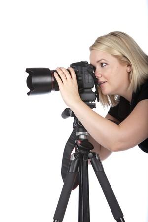 Beautiful Young Female Photographer, nehmen ein Foto mit der Kamera auf einem Stativ