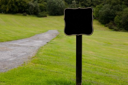 Black Sign on Grass With Forest in the Background photo