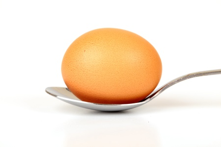 Brown Whole Egg On A Spoon Isolated On White Background Stock Photo