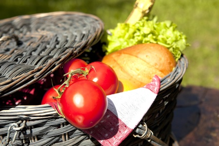 Open Picnic Basket With Tomatoes, Bread, Salad And Champagne On Old Wooden Table Stock Photo