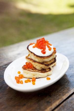 Pfannkuchen auf einem Teller mit saurer Sahne und Kaviar auf einer alten Holztisch bedeckt Lizenzfreie Bilder