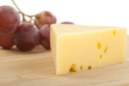 Yellow Cheddar Cheese with Red Grapes in the Background Isolated on White