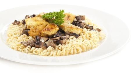 Nahaufnahme von Huhn mit Nudeln Essen, Petersilie dar�ber streuen, auf wei�en Hintergrund