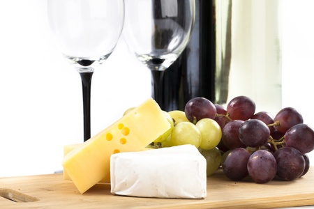 Swiss and Brie Cheese with Red and Green Grapes, Glasses and Wine in the Backround, Isolated on White