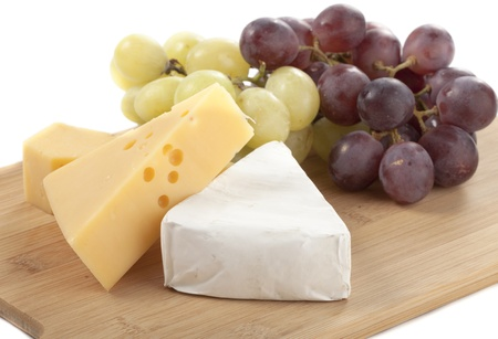 Swiss and Brie Cheese with Red and Green Grapes on White Isolated Background Stock Photo