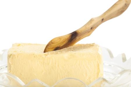 Yellow Butter mit Holz Messer auf wei�em Hintergrund
