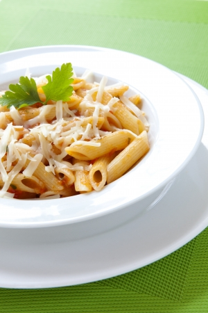 Penne Pasta with Cheese and Parsley on a White Plate
