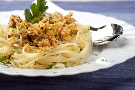Pasta with Tuna and Parsley on a White Plate with Fork and Spoon Stock Photo