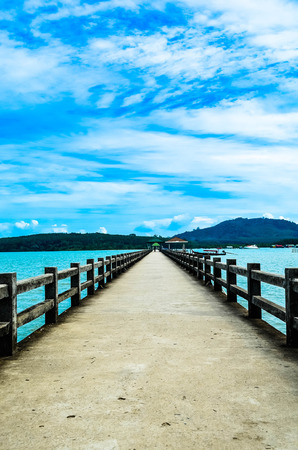 jetty over sea. turquoise water and dramatic blue cloudy.