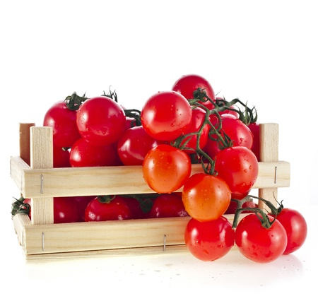 fresh ripe tomatoes in a wooden crate isolate on a white background Stock Photo