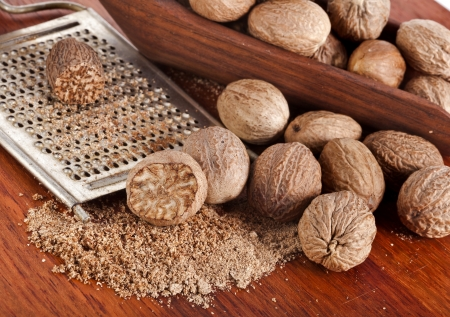 mace: nutmeg with steel hand grater on wooden background Stock Photo