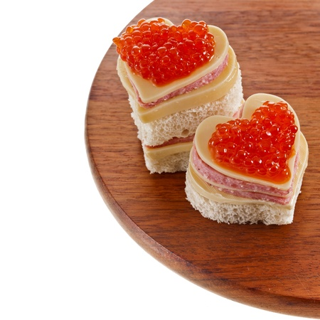 two sandwich with red caviar in the form of a heart isolated on white photo