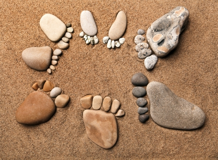 Pebble Beach: trace feet of a pebble stone on the sea sand backdrop , concept happy family