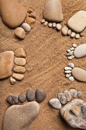 huellas pies: localizar a la familia pies de una piedra de gravilla en el fondo del mar, arena, Foto de archivo
