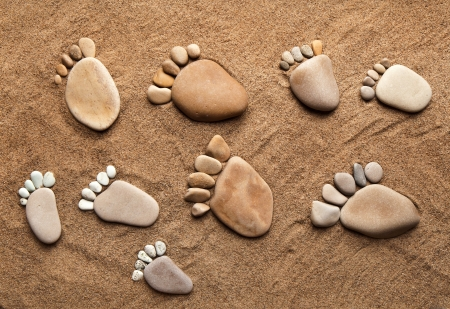 footprint sand: trace bare feet walking made of pebble stones on the beach sand background