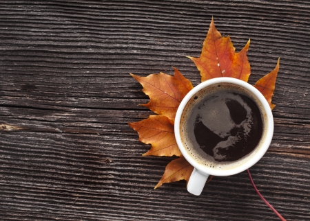 coffee cup on the autumn fall leaves and wooden surface background photo