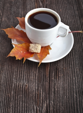 sugar maple: coffee cup on the autumn fall leaves and wooden surface background