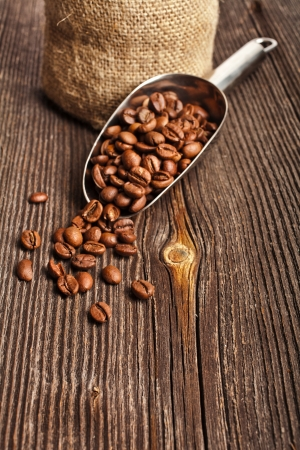 Coffee beans on vintage wooden board and metallic scoop photo