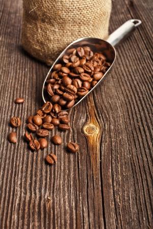 gunny bag: Coffee beans on vintage wooden board and metallic scoop