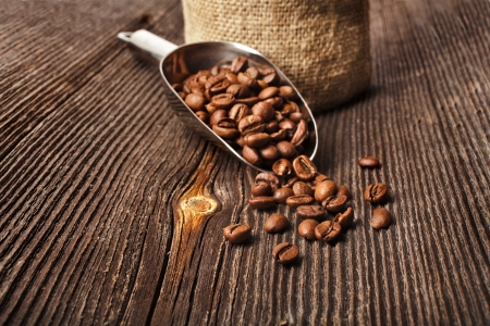 cofee cup: Coffee beans on vintage wooden board and metallic scoop