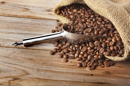 Coffee beans on burlap sack with stainless steel scoop close-up on wooden table background photo