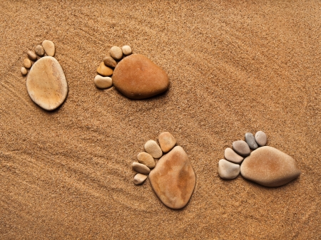 feet in sand: trace feet steps made of a pebble stone on the sea sand backdrop Stock Photo