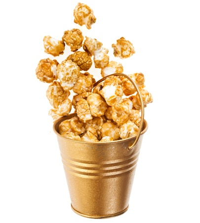 Full bucket box of caramel popcorn dropped isolated on white photo