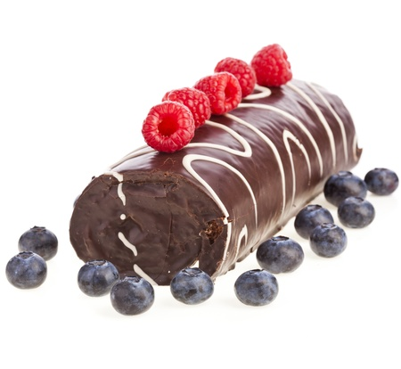 swiss roll: chocolate biscuit cake roulade with fresh berries isolated on white