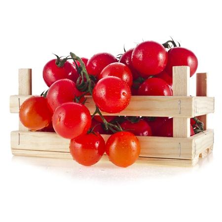 tomate cherry: tomates frescos en una caja de madera aislar sobre un fondo blanco Foto de archivo
